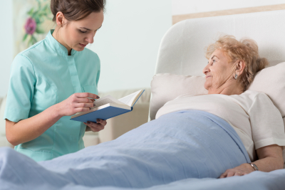 caregiver reading a book while ill senior woman listening