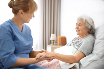 caregiver massaging the hand of the senior woman