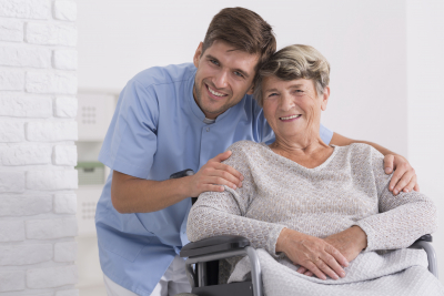 male caregiver hugging his senior woman sitting on a wheelchair
