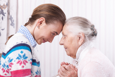 senior woman and caregiver holding hands together